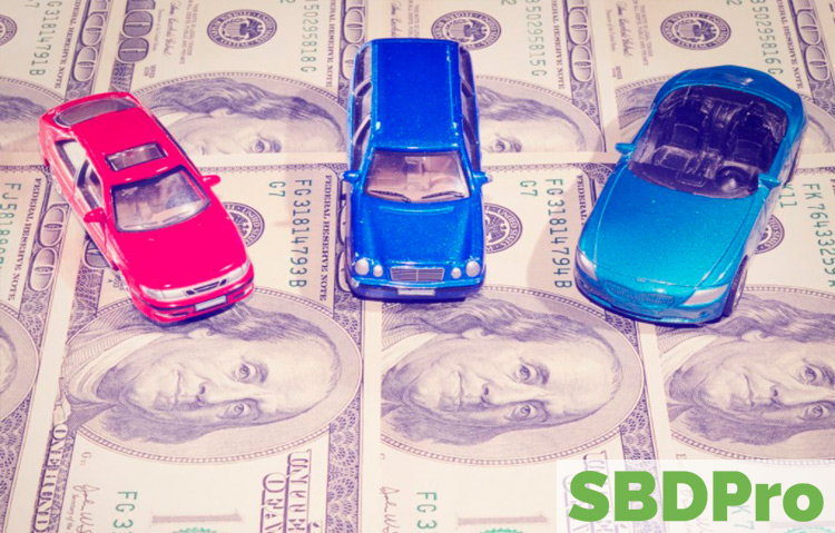 three toy cars sitting on sheet of hundred dollar bills