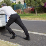 Man pushing broken down car: SBDPro Automotive Blog