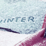the word winter written on windshield in snow