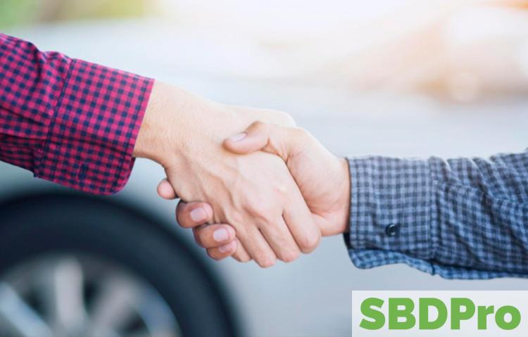 handshake in front of car