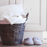 laundry basket sitting on floor, full of wool bedding, with pair of wool slippers sitting next to it